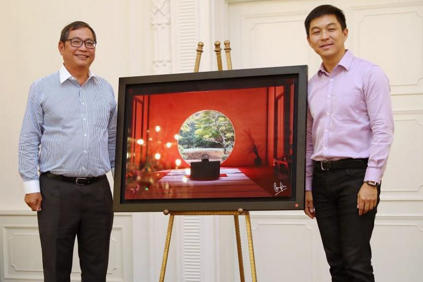 """Speaker of Parliament Tan Chuan-Jin presenting a metallic print of his photograph to Maybank Singapore deputy CEO Allen Ng during the """"Our Place in the World"""" photo exhibition high tea reception at Fullerton Hotel on April 17, 2019."""
