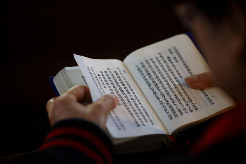 A believer reads the bible during mass at St. Joseph's Church, a government-sanctioned Catholic church in Beijing.