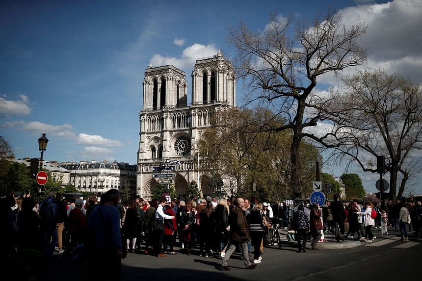 People look at Notre-Dame Cathedral two days after a massive fire devastated large parts of the gothic structure.