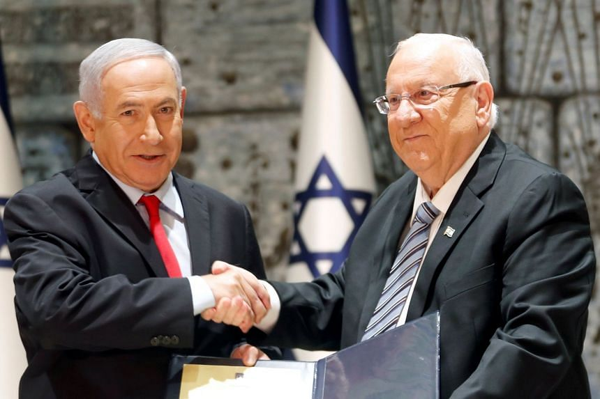 Israel's President Reuven Rivlin (right) hands a letter of appointment to PM Netanyahu.
