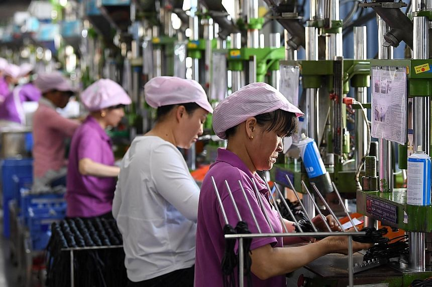 Women working on a data cable production line at a factory in Xinyu, Jiangxi province, earlier this month. Figures suggest that factory output is ticking up, shoppers are back at the tills and the world, after several tough months, is buying more Chi