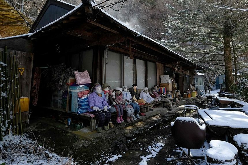 Above: Resident Tsukimi Ayano created life-sized dolls to inject some life into her depopulated village. Left: Ms Ayano making the head of a doll last month. She uses knitting wool for hair, elastic fabric for skin, and wooden sticks and newspapers t