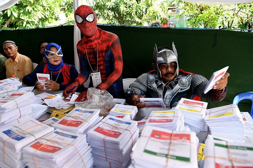 Election officials dressed in costume to match the horror theme at a polling station in Lebak Bulus, Jakarta. Officials wearing superhero costumes preparing ballot papers in Surabaya, East Java. Efforts to increase voter turnout have taken on added u