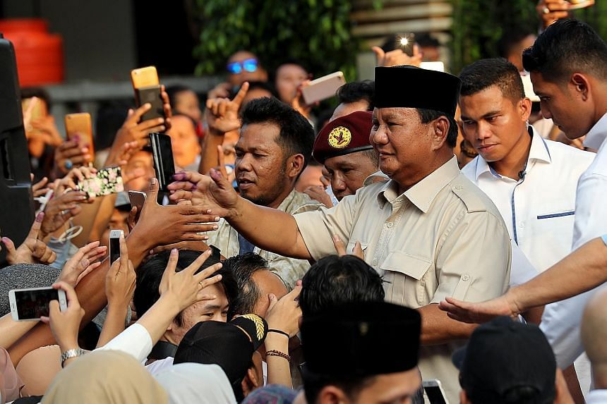 "Presidential candidate Prabowo Subianto (third from right) with supporters yesterday in Jakarta. He cast doubt on the impartiality of pollsters tasked with tallying unofficial preliminary results, and called on his supporters to keep calm and ""overse"