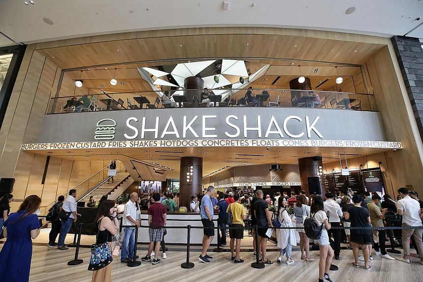 Diners queueing up for Shake Shack at Jewel Changi Airport, which opened its doors to the public yesterday. The Jewel outlet is the New York burger chain's first in Singapore. ST PHOTO: KEVIN LIM