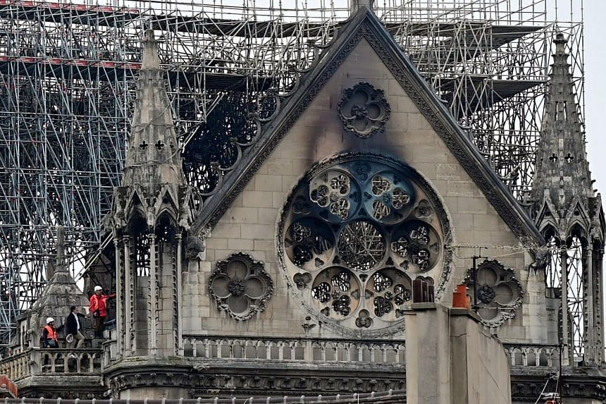 The Notre-Dame cathedral's interior (top) and its roof (above) in the aftermath of the fire that devastated it on Monday. Tycoons and international firms have promised financial and expert help to rebuild it.