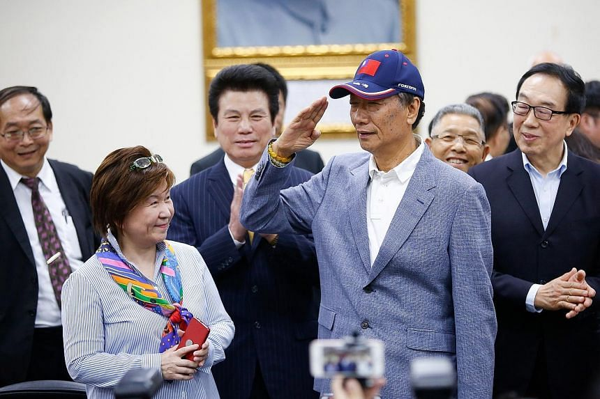 Foxconn chairman Terry Gou saluting at a media briefing at the Kuomintang party headquarters in Taipei, Taiwan, yesterday. His participation in the Kuomintang primaries shakes up a presidential race that will determine the course of the island's rela