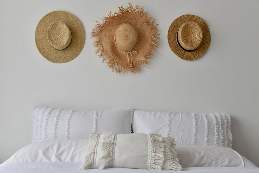 Freelance content creator Hilary See, 27, hangs up her hats with hooks she put up herself in the bedroom.