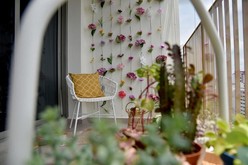 Freelance content creator Hilary See's DIY wall of hanging flowers seen behind the chair in her balcony.