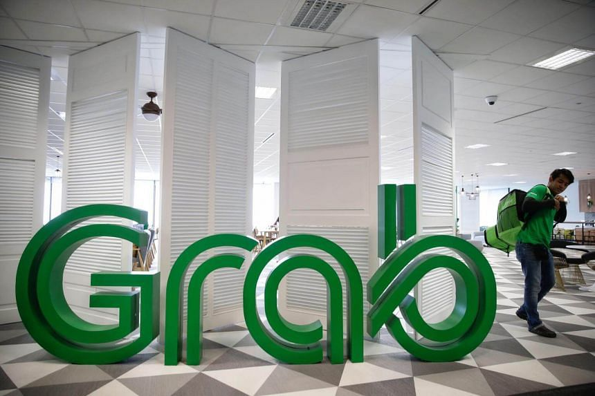 A GrabFood delivery man walking past the company logo in the new Grab office at Marina One West Tower on May 28, 2018.