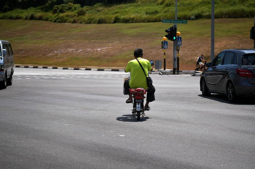 A man on an electric scooter or personal mobility device riding across a traffic junction in Tampines, on Jan 11, 2019.
