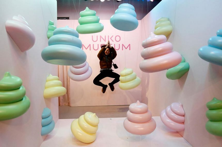 A visitor jumps to pose for a photo behind a display at the the Unko (poop) themed museum in Yokohama, Japan, on April 17, 2019.