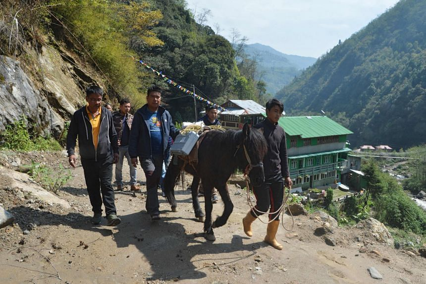 Election workers transporting electronic voting machines on horseback to the Darjeeling polling station in Srikhola, near the India-Nepal border, for the second phase of voting in the Indian elections.