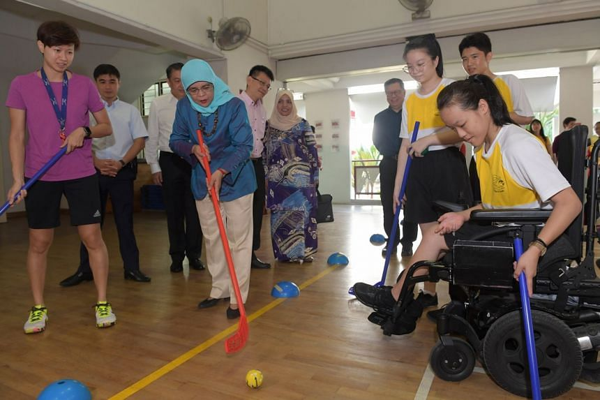 President Halimah Yacob playing floorball with Zhenghua Secondary student Eileen Tan, 16, during her community engagement visit to the school yesterday. The President has commended the school's buddy system.