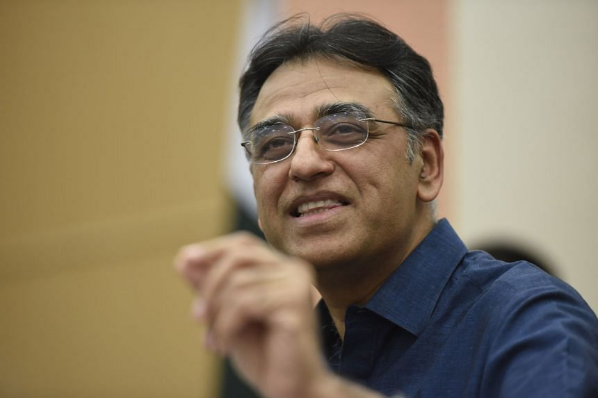 Asad Umar talks with journalists after resigning as finance minister.