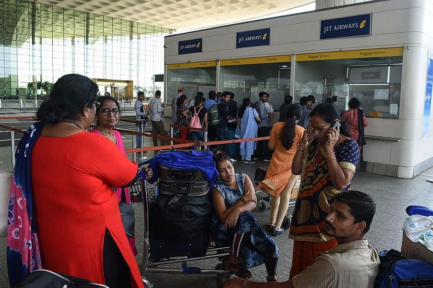 Passengers waiting by the Jet Airways ticketing counter yesterday at Chattrapati Shivaji International Airport in Mumbai. The airline's stock fell to 163.9 rupees on the Bombay Stock Exchange yesterday. It was worth more than four times that a year a