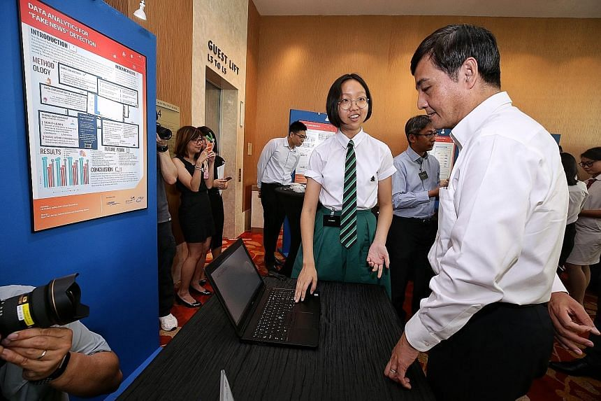 Raffles Institution student Liu Haohui explaining her project to detect fake news to Senior Minister of State for Defence Heng Chee How at the Young Defence Scientists Programme exhibition yesterday.