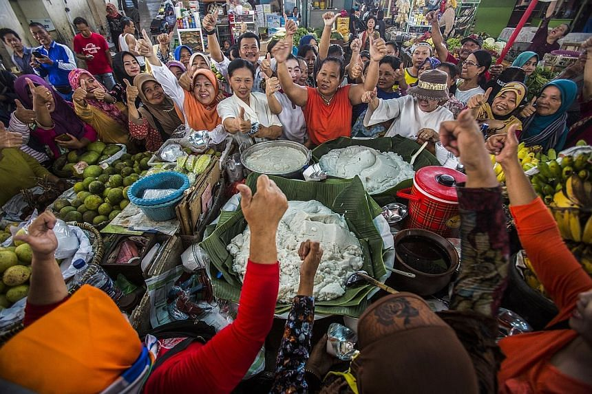 Supporters of incumbent President Joko Widodo shouting slogans yesterday as they celebrated at a local market in Solo, Central Java, after the early-count results showed he was poised to return for a second term in office. PHOTO: EPA-EFE