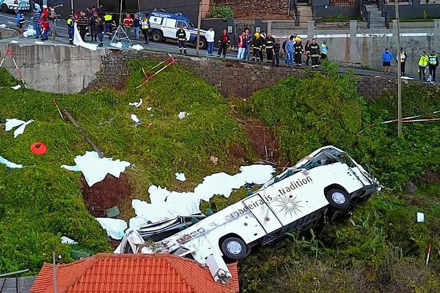 A screen grab from footage showing the wreckage after a tourist bus veered off a steep, narrow road, then plunged and overturned next to a house in the coastal town of Canico on the Portuguese island of Madeira on Wednesday. The driver had reportedly