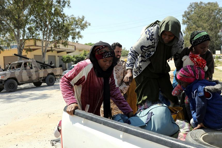 Members of the Libyan internationally recognised government forces evacuate an African family during the fighting with Eastern forces, at Al-Swani area in Tripoli, Libya, on April 18, 2019.
