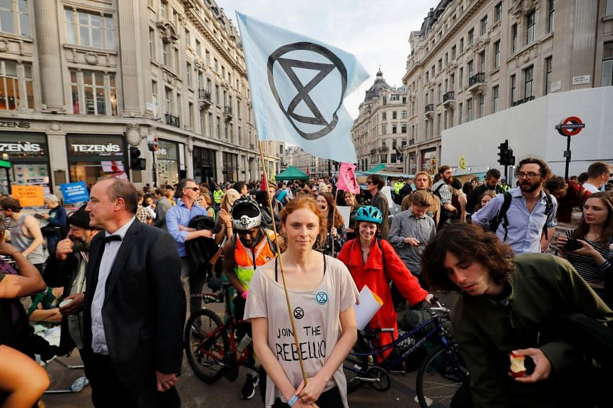 Climate change activists block the road junction at Oxford Circus in central London.