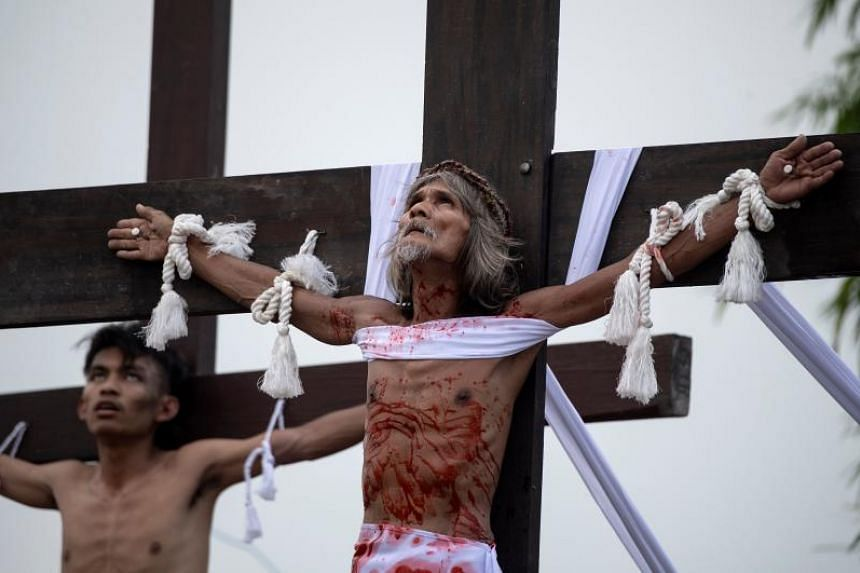 Christian devotees are nailed to a cross during a reenactment of the Crucifixion of Christ during Good Friday and ahead of Easter in San Juan, Pampanga, on April 19, 2019.