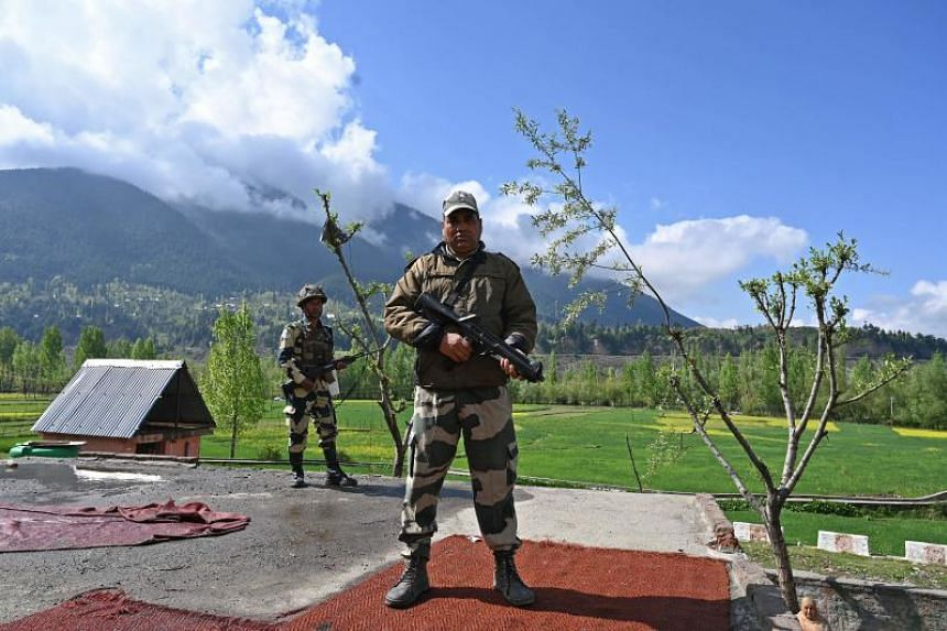 Indian Border Security Force soldiers stand guard on the top of a polling station during a second phase of elections at Kangan, some 35 km from Srinagar, on April 18, 2019.