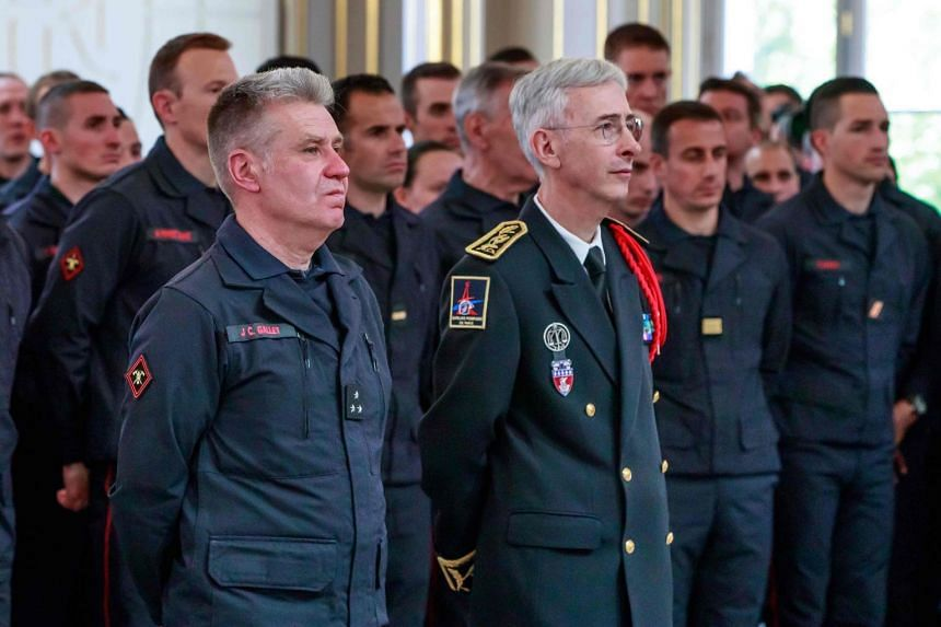 Paris fire brigade officers Jean-Claude Gallet (left) and Didier Lallement (right) listen as Macron addresses brigade staff and other emergency workers.