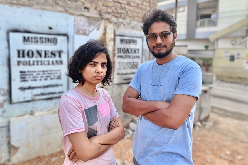 Swathi and Vijay with their artwork in the background, which urges voters in Hyderabad, capital of the Indian state of Telangana, to consider negative voting.