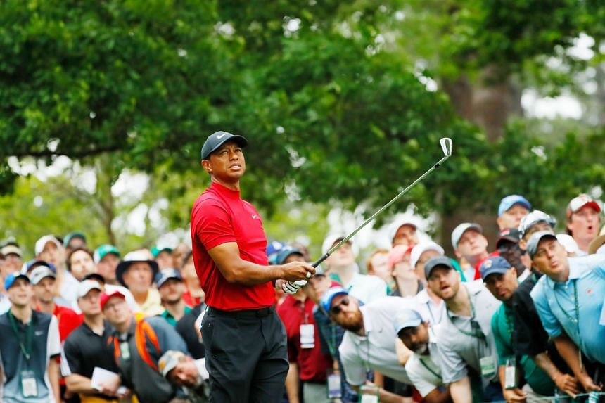 Tiger Woods watching his tee shot on the fourth hole in the final round of the Masters last Sunday. Huge crowds followed him on all four days at Augusta and roared when he won his fifth Masters and 15th golf Major. PHOTO: AGENCE FRANCE-PRESSE