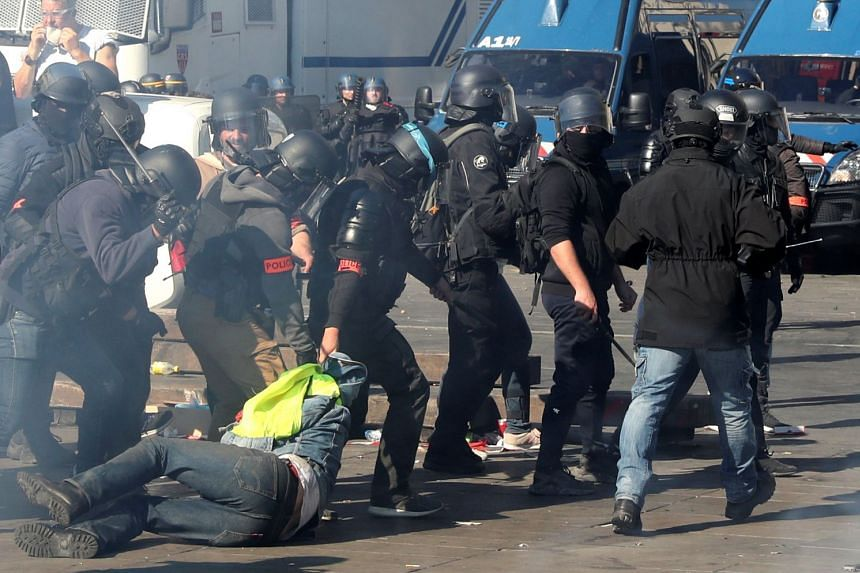 Riot police drag a protester during the demonstration in Paris.