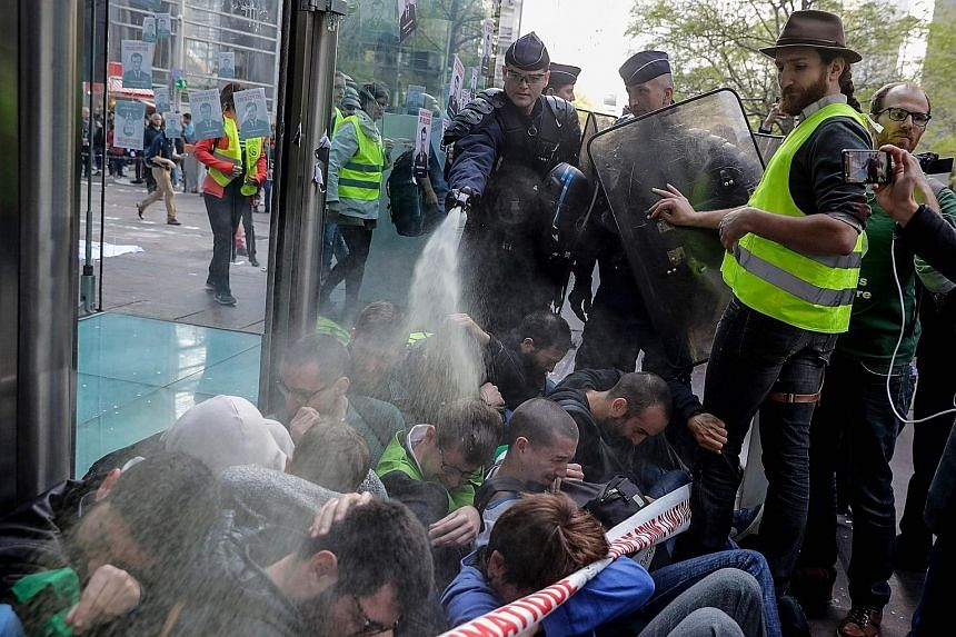 A French anti-riot police officer using pepper spray on climate-change activists as they blocked the entrance of the Societe Generale bank headquarters in a sit-down protest in Paris yesterday. PHOTO: AGENCE FRANCE-PRESSE