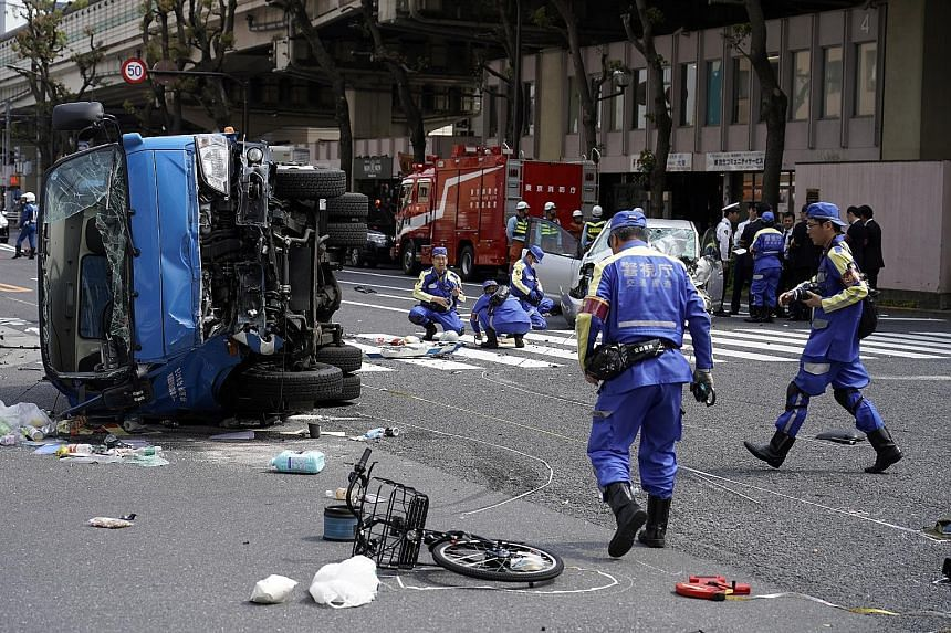 Police officers at the scene of the traffic accident in the Ikebukuro district of Tokyo yesterday. The car, driven by a man in his 80s, struck pedestrians at a busy intersection and then hit a garbage truck.