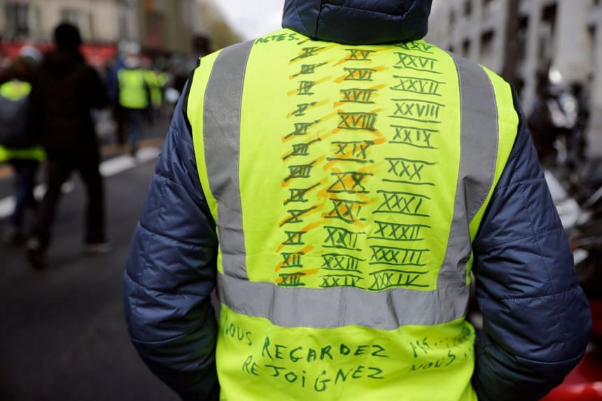 A demonstrator wears a yellow vest noted with all his attended acts and future ones as he and thousands march on April 13, 2019 in Paris.