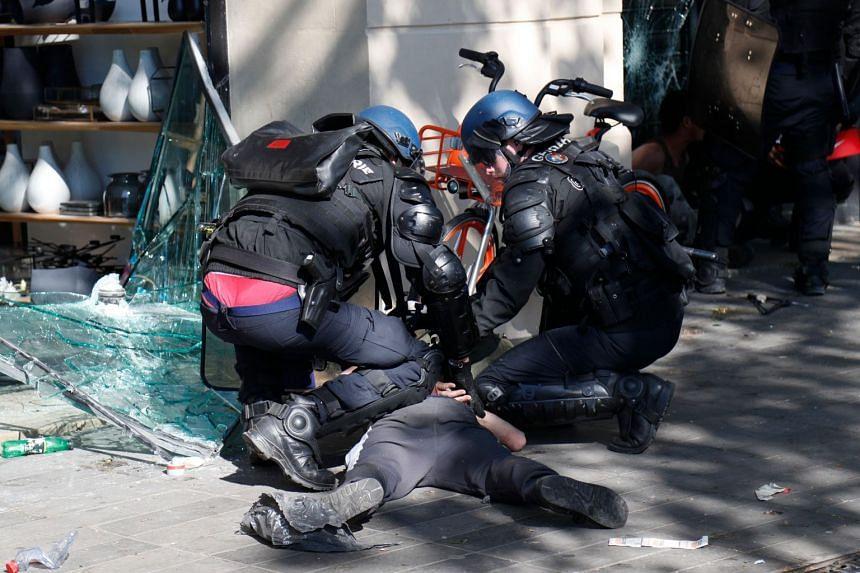 Anti-riot police arrest a protester at the Place de la Republique.