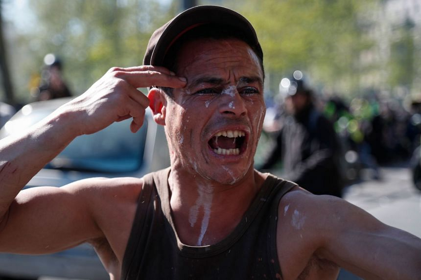 A man reacts after receiving tear gas in his face during clashes with riot police at the Place de la Republique.