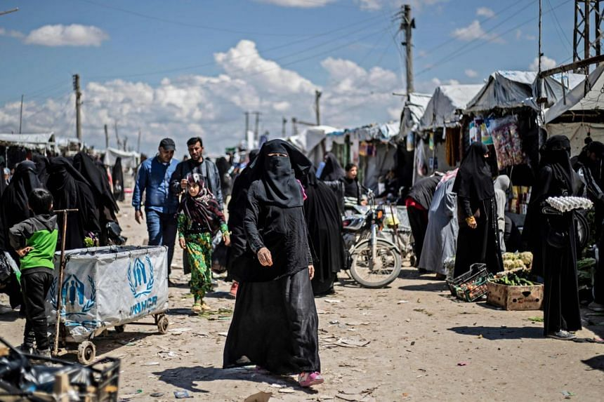 Women displaced from Syria's eastern Deir Ezzor province, walk in a market inside the al-Hol camp for displaced people, in al-Hasakeh governorate in north-eastern Syria, on April 18, 2019.