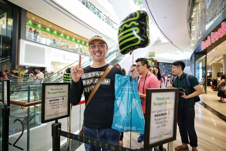 Mr Justin Zheng (above), who works in the aviation industry, was the first person in the queue outside Shake Shack when it opened at Jewel Changi Airport on Wednesday. Queueing service provider iQueue was hired by a radio station to buy food from the burg