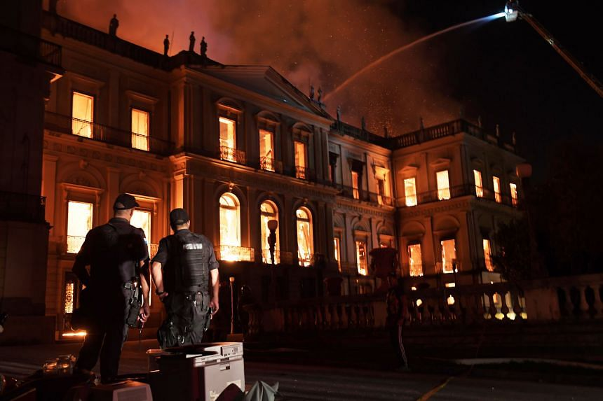 Policemen watching as a massive fire engulfed the National Museum in Rio de Janeiro, one of Brazil's oldest buildings, on Sept 2 last year. The 200-year-old institution was considered the main natural history museum in Latin America.