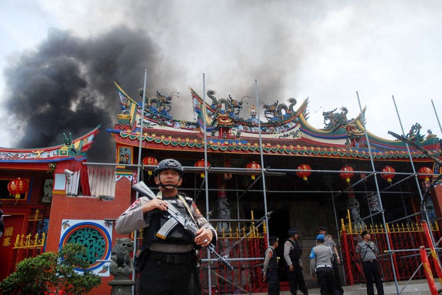 Indonesian policemen standing guard as firefighters worked to control a blaze at the Samudra Bhakti temple in Bandung on the first day of Chinese New Year on Feb 5. The fire was allegedly caused by lit prayer candles inside the temple that had been b