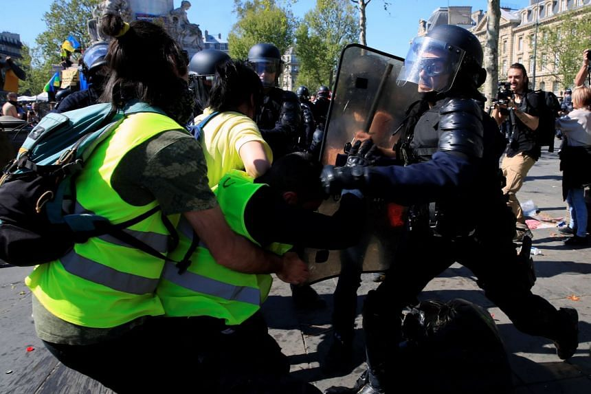 A protester scuffles with a police officer.