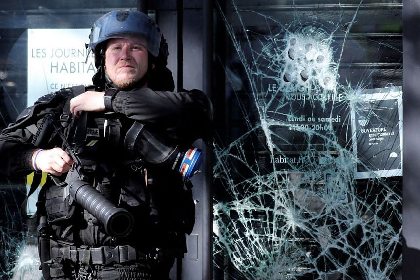 A police officer stands in front of a damaged window during the protests.