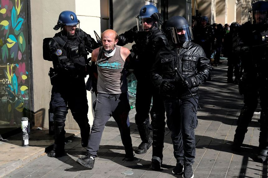 Police officers detain a protester.