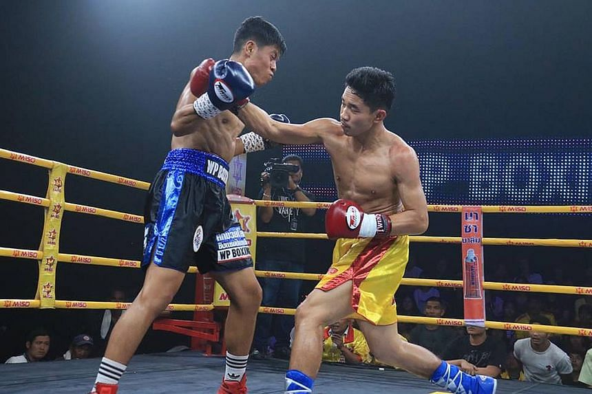 Singapore's Muhammad Ashiq (left) in action against Thailand's Thattana Luangphon in Bangkok's Workpoint Studios yesterday. PHOTO: FACEBOOK/WP BOXING