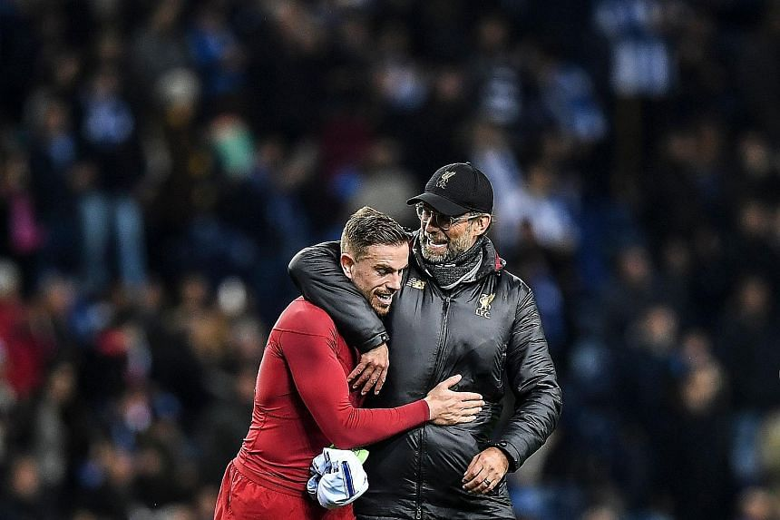 Liverpool midfielder Jordan Henderson celebrating with manager Jurgen Klopp after the 4-1 Champions League quarter-final, second-leg win over Porto on Wednesday. The Reds will meet Barcelona next in the semi-finals of the competition. PHOTO: AGENCE F
