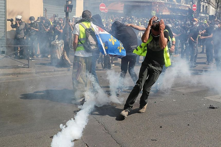 Protesters running away from a cloud of tear gas at a demonstration during the 23rd consecutive Saturday of protests by the Yellow Vest movement in Paris yesterday. PHOTO: REUTERS