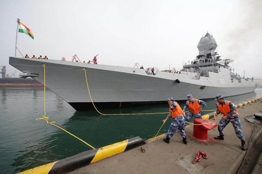 Chinese navy personnel moor the Indian Navy warship INS Kolkata at Qingdao Port, on April 21, 2019.