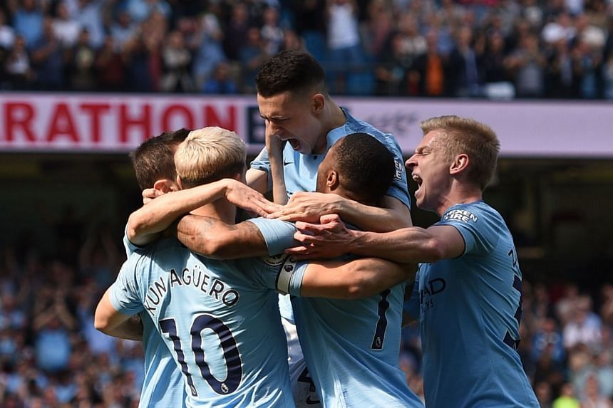 Manchester City's English midfielder Phil Foden (centre) celebrating with his teammates after scoring the opener in the 1-0 Premier League win over Tottenham at the Etihad Stadium yesterday. City moved back to the top of the table, one point ahead of