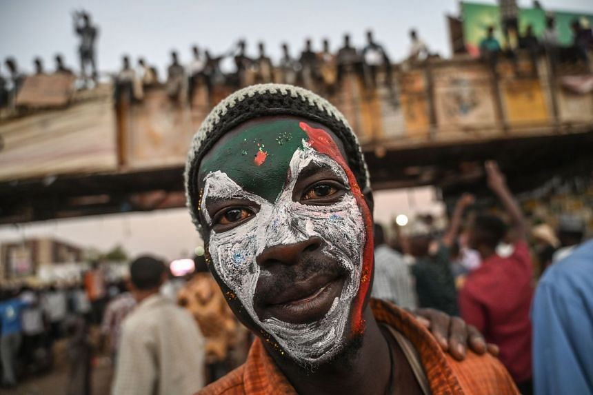 A Sudanese protester poses with a Sudan national flag painted on his face in Khartoum.