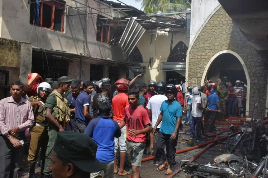 Police officers and residents gathering at the Secon church in Batticaloa following an explosion, on April 21, 2019.
